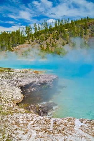 pressurized: Rocky rugged edge of beautiful blue geyser in yellowstone  Stock Photo