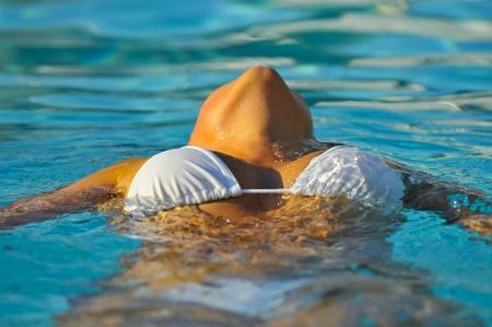 Flicka klädd vit bikini koppla av i poolen