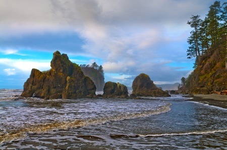 Rugged, rocky coast of Ruby Beach with dramatic clouds at sunset photo