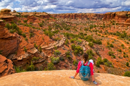 Hiking Girl sittin on the edge of the cliff on Elephant Hill Canyonlands Needles District Utah