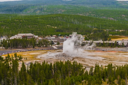 Famous Old Faithful Geyser while erupting taken from the Overlook during stormy weather