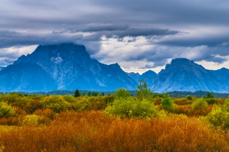 Beautiful fall colors and dramatic sky over Grand Teton Mountains - Willow Flats photo
