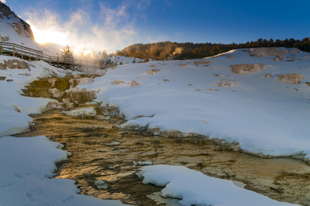 winter sunrise: Hot steaming water beautiful cascade geyser - winter landscape in Yellowstone National Park Stock Photo