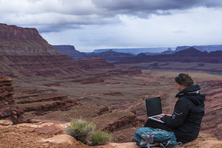 Girl Hiker on top of the mountain with her laptop computer