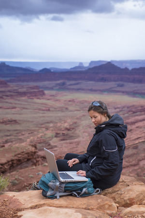 Girl Hiker on top of the mountain with her laptop computer photo