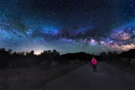 明るい銀河を見て道の真ん中に立っている女の子 写真素材