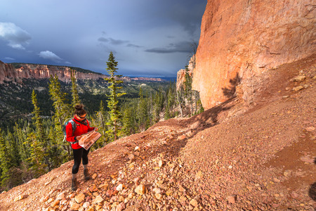 plateau point: Woman Backpacker hiking down the Ponderosa Canyon Bryce National Park