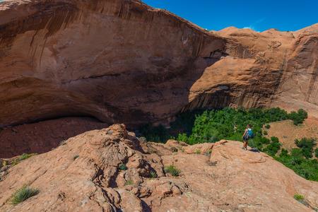escalante: Woman Hiker Backpacker hiking down the steep slick rock at Jacob Hamblin Arch Coyote Gulch Escalante National