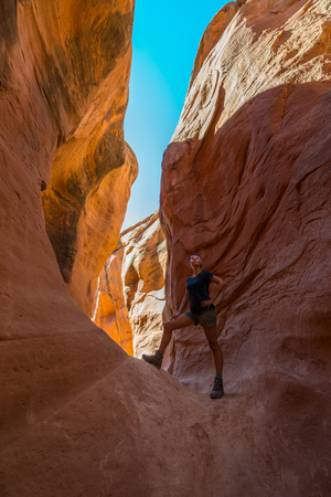 slot canyons: A woman admires the warm light in Peekaboo Gulch in the Escalante Canyons of Grand Staircase Escalante National Monument, Utah.