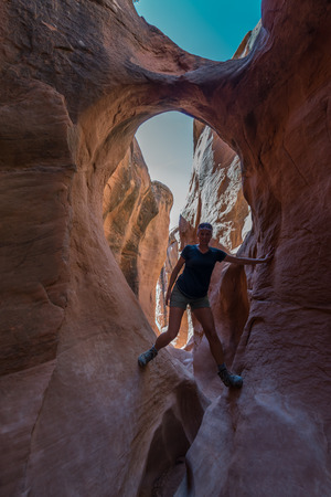 slot canyons: Girl Hiker Climbing Narrow Park of Peekaboo Gulch Canyon