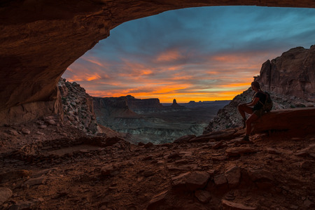 unexplored: Girl Backpacker looking at beautiful sunset from inside of the False Kiva Canyonlands National Park Moab Utah USA Stock Photo