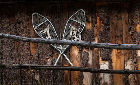 log cabin in snow: Vintage Snow Shoes on a log cabin wall Stock Photo