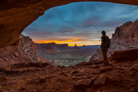 kiva: Girl Backpacker looking at beautiful sunset from inside of the False Kiva Canyonlands National Park Moab Utah USA Stock Photo