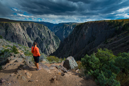 point of view: Tourist looking down the canyon Tomichi Point view of layers of cliffs at Black Canyon of the Gunnison Stock Photo