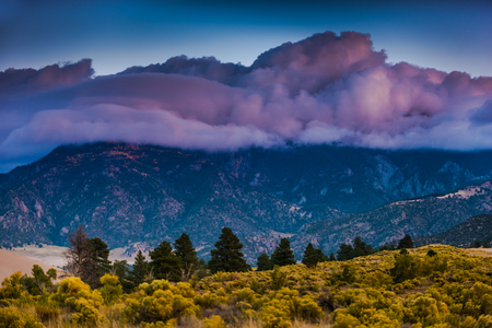 cristo: Thick clouds at Sunrise over the sangre de cristo mountains and the great sand dunes Stock Photo