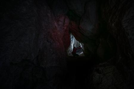 cave exploring: Woman Caver Spelunker exploring inside of a Dark Cave