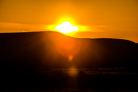 extreme heat: Sun setting behind the mountain Utah desert