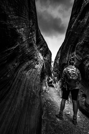 Hiker inside slot canyon Black and White hight contrast vertical composition Stock Photo