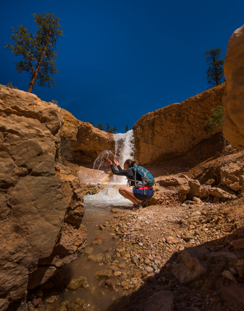 cave exploring: Backpacker Girl Exploring Bryce Canyon Waterfall near Mossy Cave USA travel landscapes