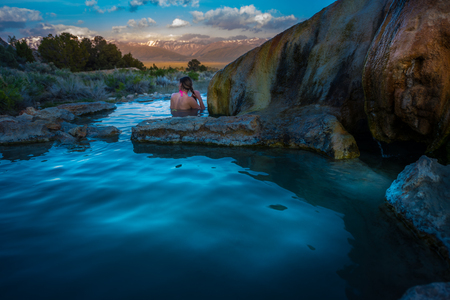 sierras: Woman relaxes in Travertine Hot Springs California USA