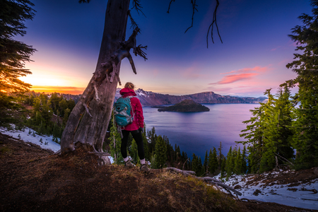 Backpacker Girl Looking at Crater Lake at Sunset Wizar Island and Watchman Peak in the Background Stock Photo