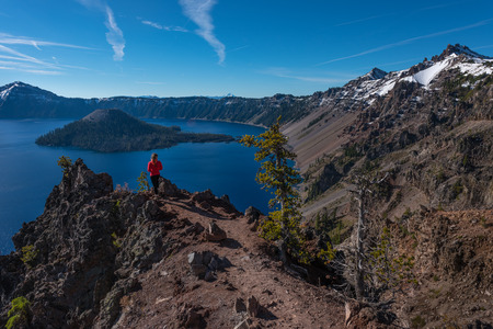 Tourist admiring Crater Lake as seen from Merriam Point with wizard island The Watchman and Hillman Peak