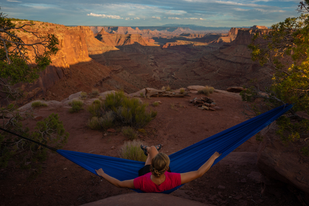 Hiker rests on a hammock admiring the sunset East Fork Shafer Canyon near Dead Horse Point State Park Canyonlands Utah Stock Photo