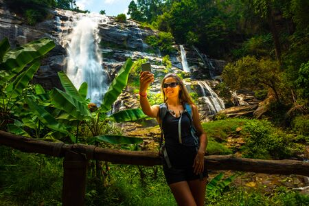 Young woman wearing sunglasses takes selfie on her smartphone with Wachirathan waterfall in the background Doi Inthanon National Park near Chiang Mai Thailand. Stock Photo