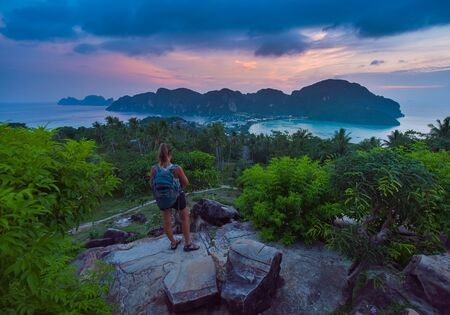 Young woman with backpack admires landscape of the Ko Phi Phi Don View from the top of the hill after sunset, Thailand