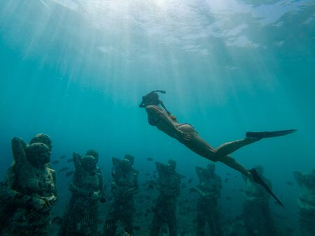 Young girl freediving too see underwater sculptures in Gili Meno Indonesia