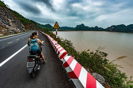 Cat Ba Island Vietnam Tourist Girl on a scooter wearing backpack admires a beautiful view of Ha Long Bay
