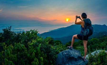 Tourist in Vietnam Backpacker taking a picture of The Da Nang Bay and Ba Na mountains from the viewpoint