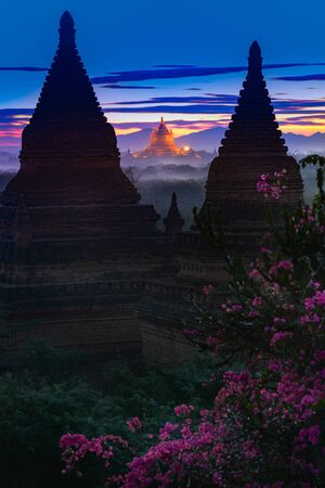 Bagan Myanmar Golden Temple between two Bell-shaped pagodas after sunset  Imagens