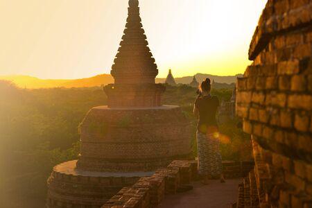 Bagan Myanmar Young Woman photographs Beautiful Stupas at Sunset  版權商用圖片