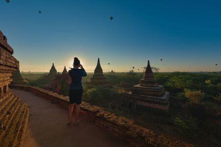 Bagan Myanmar Young Woman photographs Beautiful Stupas and hot air balloons at Sunrise