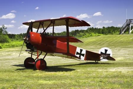 aileron: Classic Red Barron Fokker Dr 1 triplane on grass runway