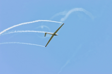 airshow: Glider performing aerobatics with smoke trails at airshow  Stock Photo