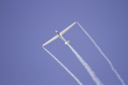Glider performing aerobatics with smoke trails at airshow  photo