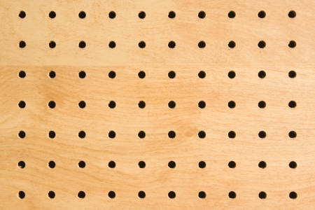 Pegboard holes used for hanging and storing tools and eguipment