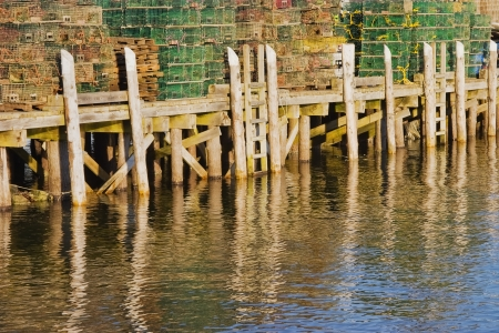 Lobster fishing traps stacked on commercial pier on coast of Maine  photo