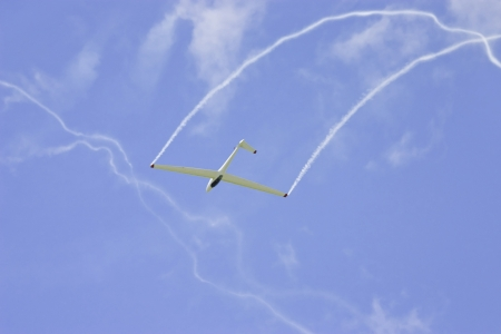 Glider performing aerobatics with smoke trails at airshow
