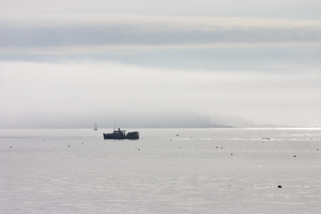 lobster boat: Morning fog lifting over lobster boat and Cranberry Island, Mount Desert Island, Maine