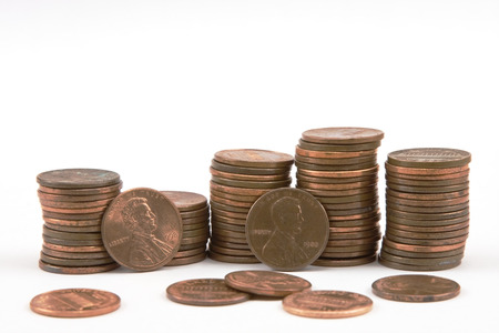 penny pinching: Stacks of pennies on white background