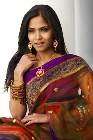 A portrait of a young, 30 something, Indian woman with long black hair, dressed in purple and gold traditional Indian attire (sari) against a white background  photo