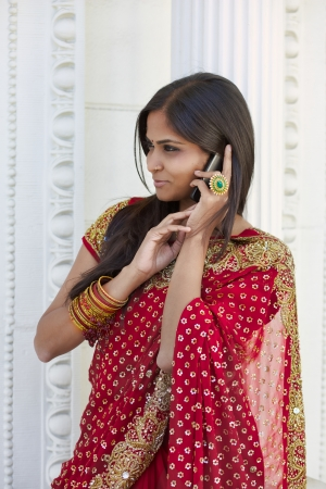 30 something: A young, modern, 30 something, Indian woman with long black hair, dressed in traditional Indian attire (sari), is amused by who ever she is talking to on her cell phone