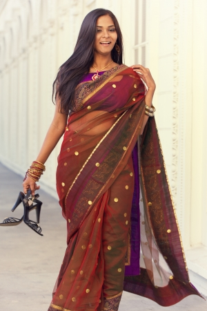A young, modern, 20 something, Indian woman with long black hair, dressed in traditional Indian attire (saree), holds her shoes as she walks down a long white hallway with repetitive arches, processed for a slight vintage effect