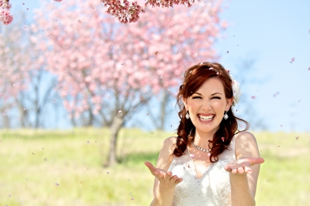 A young 20 something bride is exhilarated by being showered by cherry blossom petals. Photograph features a cherry blossom background photo