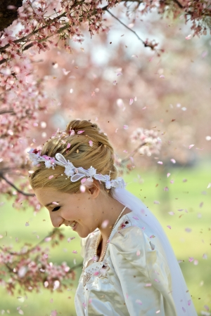 A young, 20 something blond woman in a silky, white wedding dress and veil is showered by petals from the blooming cherry blossom tree she is standing under