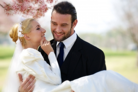 30 something: A young 20 something blond woman in a silky white wedding dress, held by her 30 something groom, whispers in his ear as they stand under a blooming cheery blossom tree.