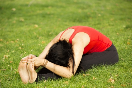 woman wearing a red sleeveless top and black pants practices yoga on the grass in a park